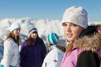Teenage girl in ski clothes looking at camera, friends in background