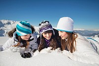 Three teenage girls in ski clothes, lying in snow