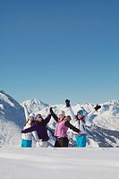 Four teenage girls in ski clothes, having fun in snow