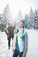 Young woman in winter clothes smiling at camera, man holding skis in background