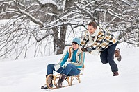 Young man pushing woman on sled