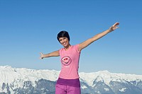 Young woman with arms raised, smiling at camera, mountains in background (thumbnail)