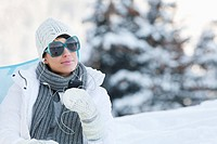 Young woman listening to MP3 player in snow (thumbnail)