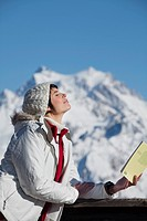 Young woman with book, enjoying winter sun, mountains in background