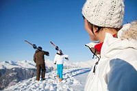 Woman looking at father and daughter carrying skis (thumbnail)