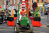 Dublin, ireland, a man in costume driving a green tractor pulling a float in a parade on o´connell street