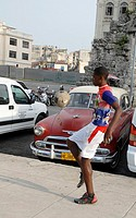 Young Cubans plays football in a park, with a classic car in the backgroundon, in Havana, Cuba
