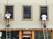 Two painters on ladders painting the window frames of an historic shop warehouse in Melville Street, Hobart, Tasmania
