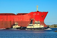 a huge cargo ship with two tug boats entering the harbour at Newcastle, NSW, Australia
