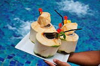 Coconuts with straws on a platter