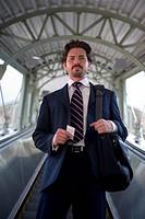 Businessman standing one escalator