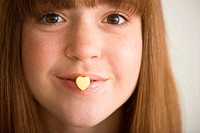 Young woman with heart shape candy on her lips
