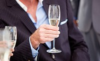 Close_up of a senior businessman holding a glass of Champagne in the office