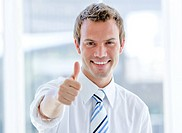 Portrait of a cheerful businessman with a thumb up in the office