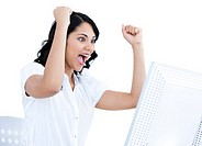 Enthousiastic businesswoman punching the air in front of her computer in the office
