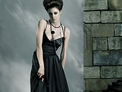 High fashion photo of a beautiful woman wearing long black dress