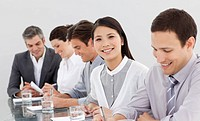 Smiling business partners taking notes in a meeting in the office