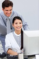 Cheerful businesswoman helping by her manager in the office