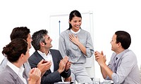Victorious businesswoman applauded for her presentation against a white background