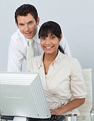 Afro_American businesswoman and caucasian businessman in the office using a laptop