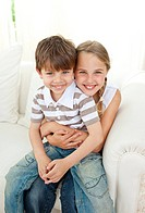 Cute girl hugging her little brother sitting on the sofa