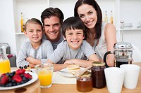 Smiling family having breakfast together in the kitchen