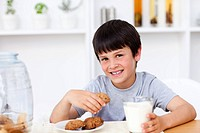 Smiling boy eating cookies in the kitchen
