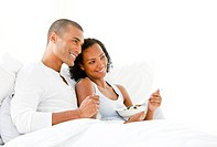 Loving couple having breakfast lying on their bed at home