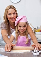 Smiling mother and daughter baking in the kitchen
