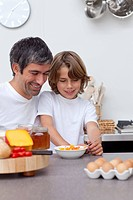 Smiling father and son having breakfast together in the kitchen