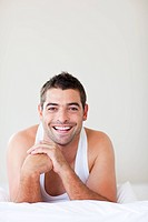 Attractive man in bed smiling to the camera