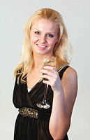 Attractive well_dressed woman holding a glass of champagne and looking at the camera with focus on woman