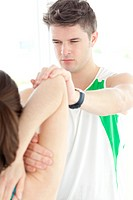 Concentrated physical therapist checking a womans shoulder during a medical exam