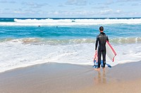 Surfer at the beach of La Pared,, Fuerteventura, Spain, rear view