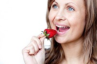 Young woman eating strawberries against a white background