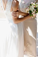 Mother hugging bride on wedding day