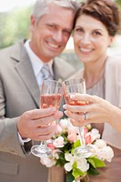 Mature bride and groom toasting with champagne