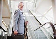 Businessman standing near escalator