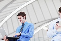 Businessman standing and using laptop