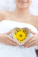 Close_up of a woman holding a bowl in the shape of a heart with a flower in a Spa center