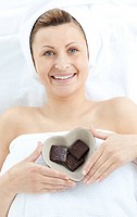 Cheerful woman holding a bowl in the shape of a heart with chocolate in a Spa center