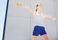 Woman using hand weights outdoors (thumbnail)