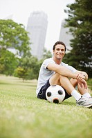 Man sitting in urban park with soccer ball
