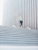 Woman running down urban staircase