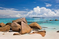 Granite boulders on the shore at Anse Lazio, island of Aride visible on horizon, Baie Sainte Anne district, Island of Praslin, Seychelles, Indian Ocea...
