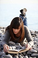 Frau mit Urlaubslektüre am Meer