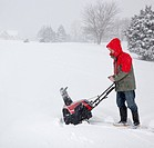 Man using snow blower on snowy drive
