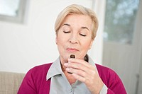 Close_up of a woman smelling aromatherapy oil