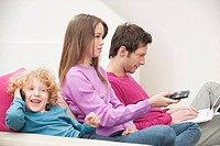Family sitting together involved in different activities (thumbnail)