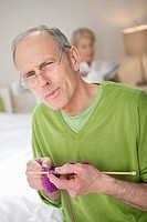Portrait of a man knitting with a woman in the background